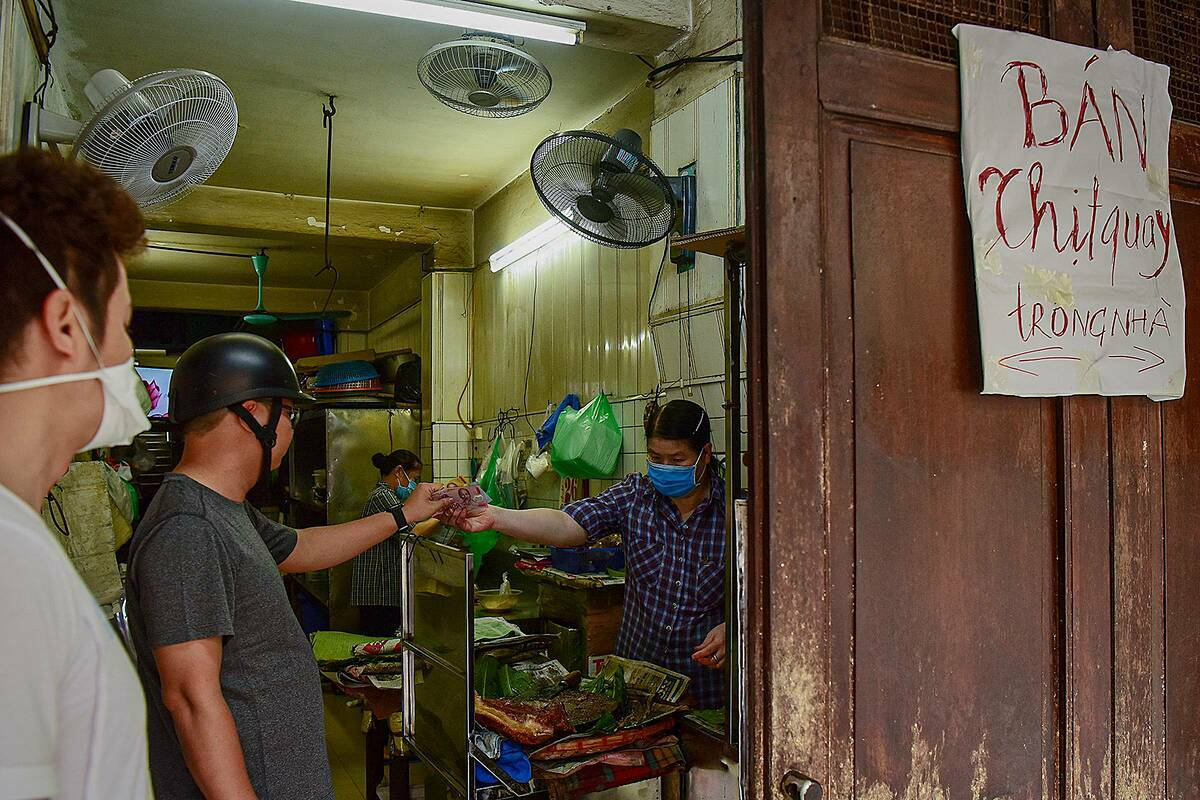 A roast pork stall on Hang Buom Street closes its front but continues to do business inside (?? Door's wide open!!).