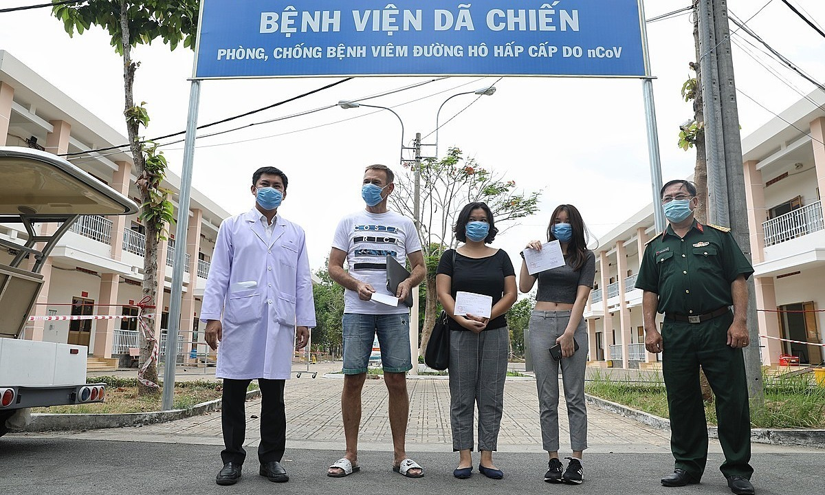 Three Covid-19 patients (C) leave Cu Chi field hospital after recovery, March 30, 2020. Photo by VnExpress/Huu Khoa.