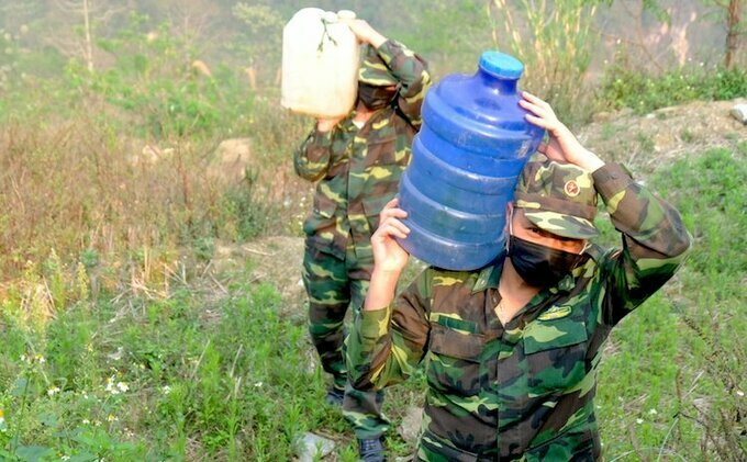 Lieutenant Colonels Dinh Cong Vy and Tong Hong Van at checkpoint 168(2) use cans to transportwater from the spring. Photo by VnExpress/Gia Khau.