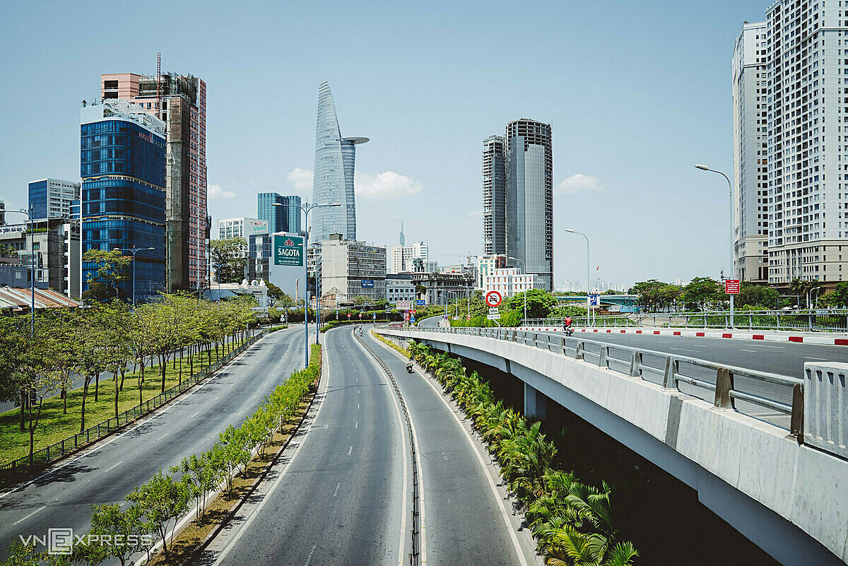 Wide and empty roads heading toward Thu Thiem Tunnel, with Bitexco Tower can be seen in the distance. Bitexco Tower is one of the symbolic buildings of Saigon with 68 floors, 262.5 m high.