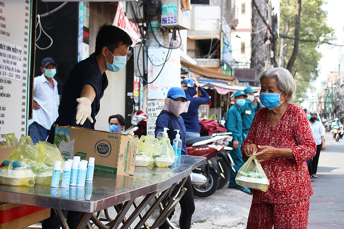 Apart from food and milk, peoplearegiven a bottle ofdonatedhand sanitizer.Those without a mask are also generously supplied. Photo by VnExpress/Diep Phan.