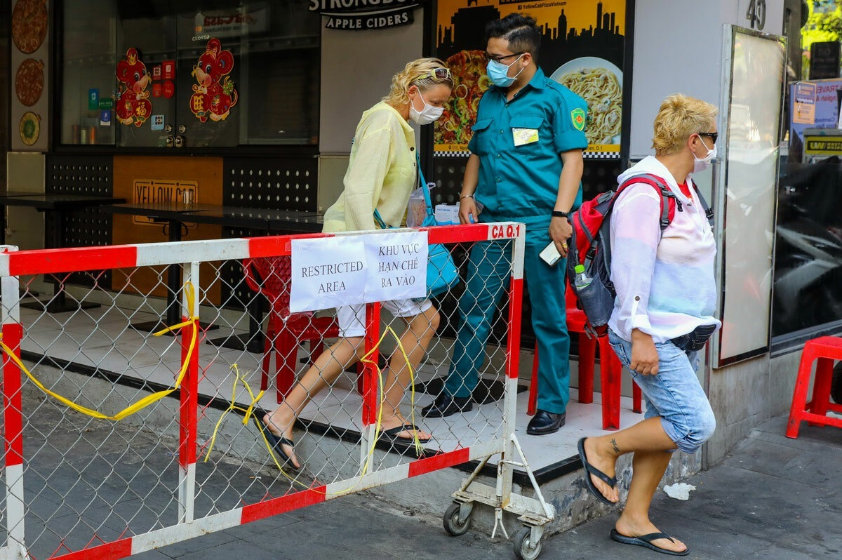 Foreigners leave an alley on Bui Vien Street, District 1, Ho Chi Minh City on March 15, 2020 after a Latvian tourist staying here tested positive with the novel coronavirus. Photo by VnExpress/Quynh Tran.