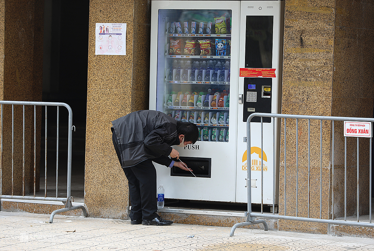 A man uses a stick to get his bottle of water from a vending machine outside Dong Xuan Market.
