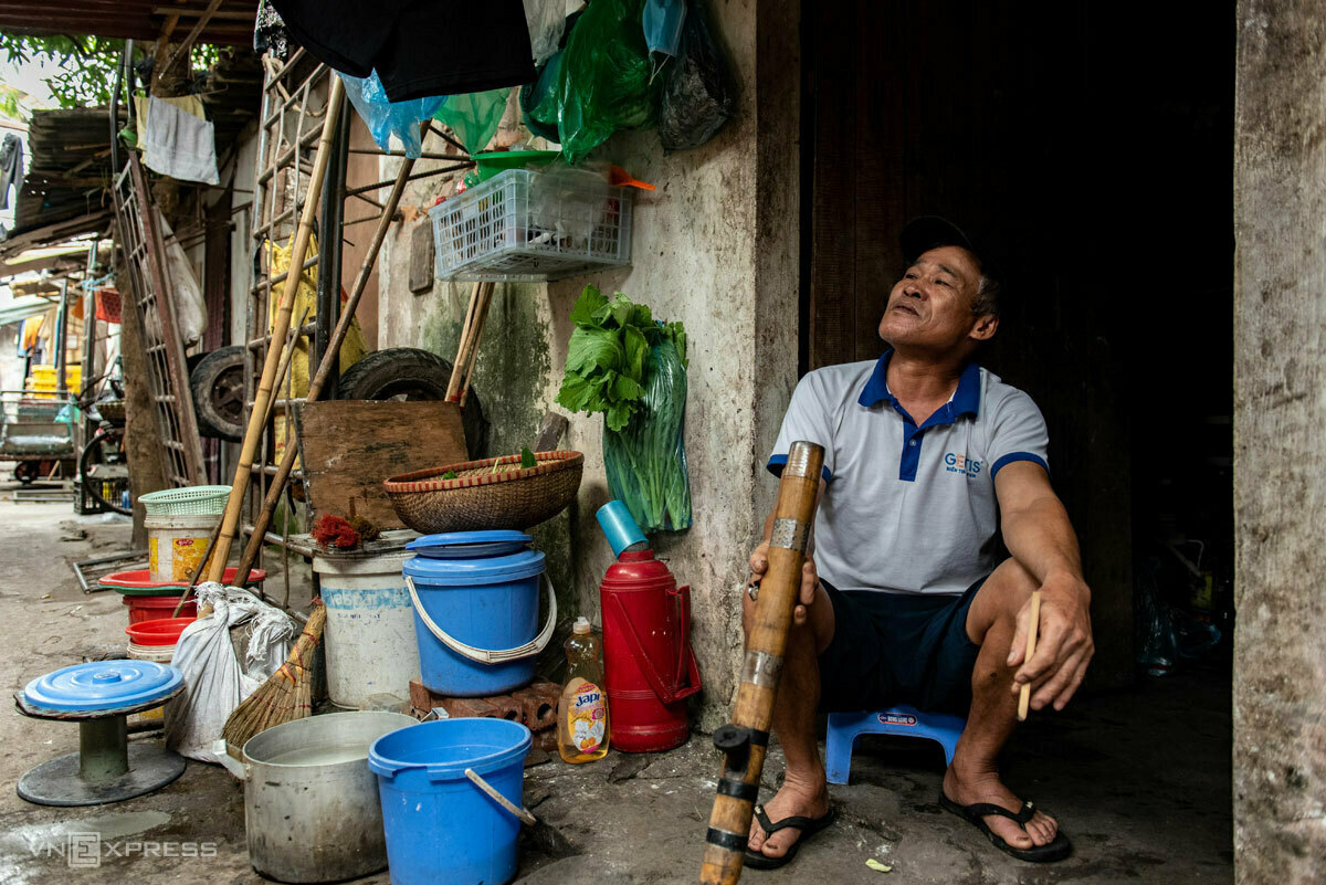 Nguyen Van Chi smokes tobacco from a bong in front of his rented room in a slum next to Hanois Long Bien Bridge. Photo by VnExpress/Thanh Hue