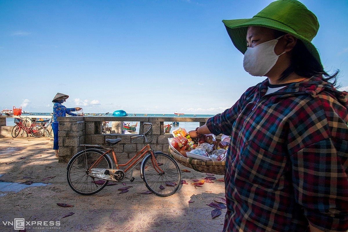 A street vendor wearing a face mask seeks customers at Front Beach on April 2. All popular tourist destinations in the country have been closed since mid-March while bars and most other entertainment facilities were shut until April 15 on the Prime Minister's orders, with the country having entered a nationwide social distancing campaign.Vietnam has recorded 251 Covid-19 infections cases as of Wednesday morning. Of them, 122 have been discharged, including 27 on Tuesday.