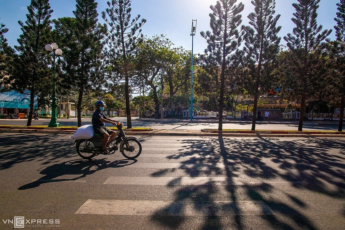 A man wearing a face mask carries goods on a motorbike on Quang Trung Street with less traffic on the morning of April 2.