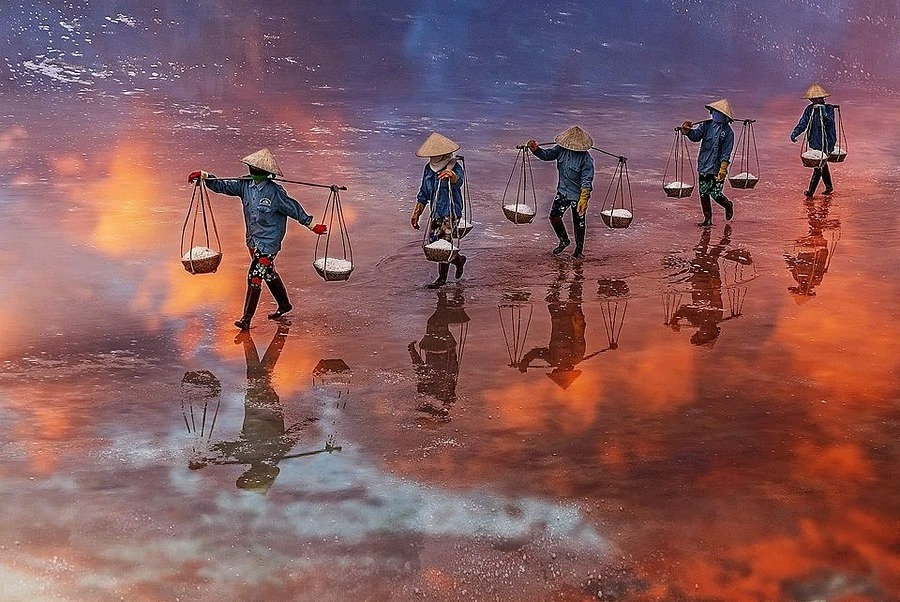 Sunset on a salt field in NinhHoa District in the central province of Khanh Hoa, home to the famous Nha Trang beach town, taken by Tuan Ngoc.These female workers carry salt all day long, in the heat of the sun, Ngoc said.