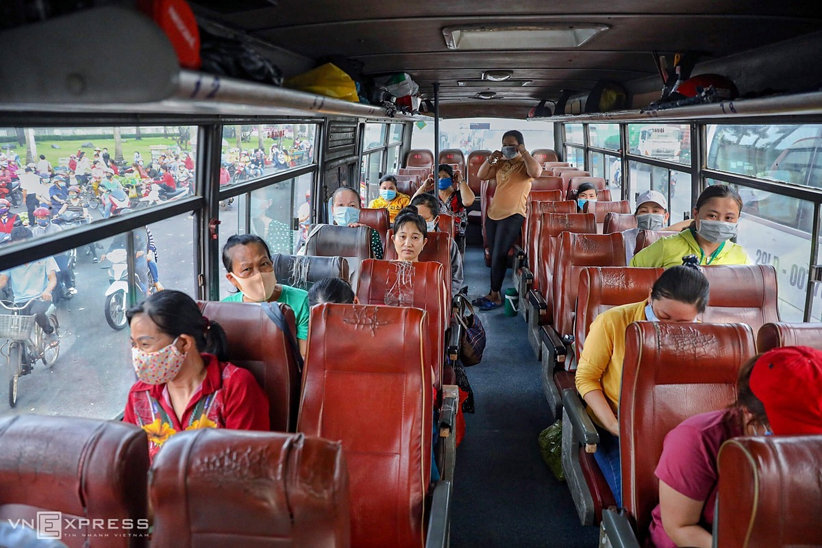 Workers sit apart from each other on the bus.