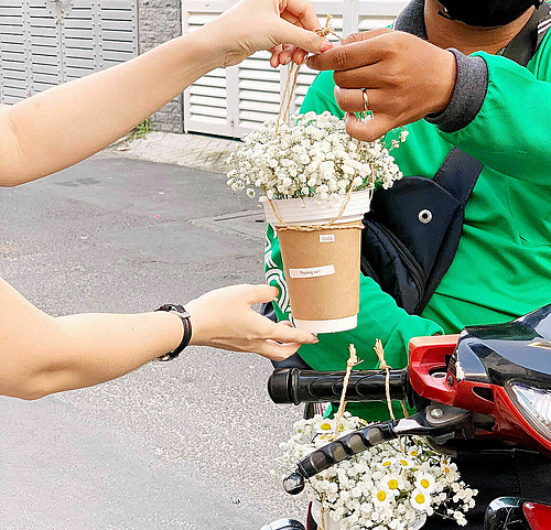 An employee of Quala flower shop hands Hoa Coffee to a delivery driver. Photo by VnExpress/Duc Thanh.