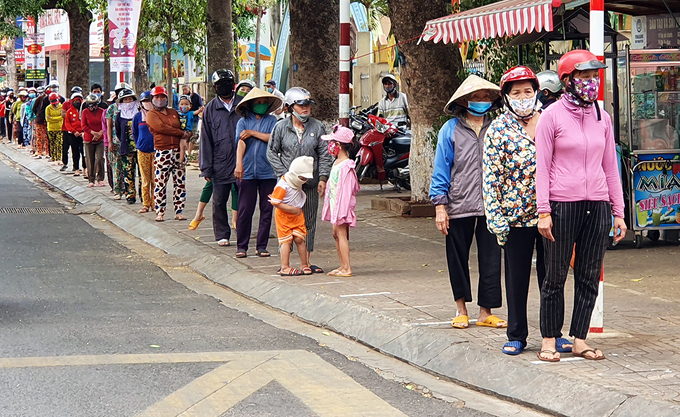 People wait in line to receive rice in Dak Lak on April 13. Photo by VnExpress/Ngoc Oanh.
