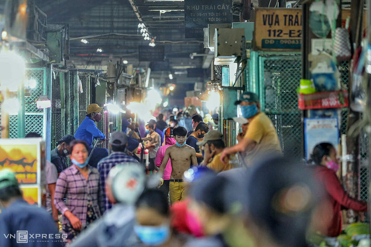 In late night, the entrance to the market was flooded with huge crowds.Our specific job is to transport goods, trade and exchange goods with customers. How to communicate with each other if standing so far away, said Viet, a porter.