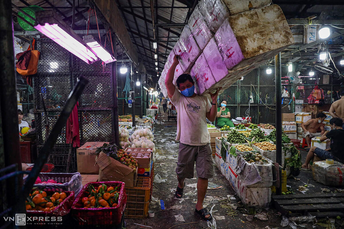 A man in mask carries foam boxes to the container area to transfer the fruits to his stall.