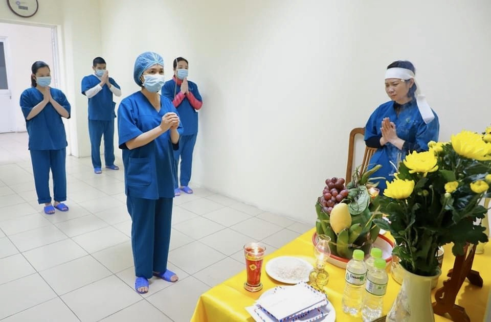 Hoang Thi Thu Huong (right) and her colleagues mourn her fathers death in front of his altar that her hospital helps set up. Photo courtesy of Hospital No.2
