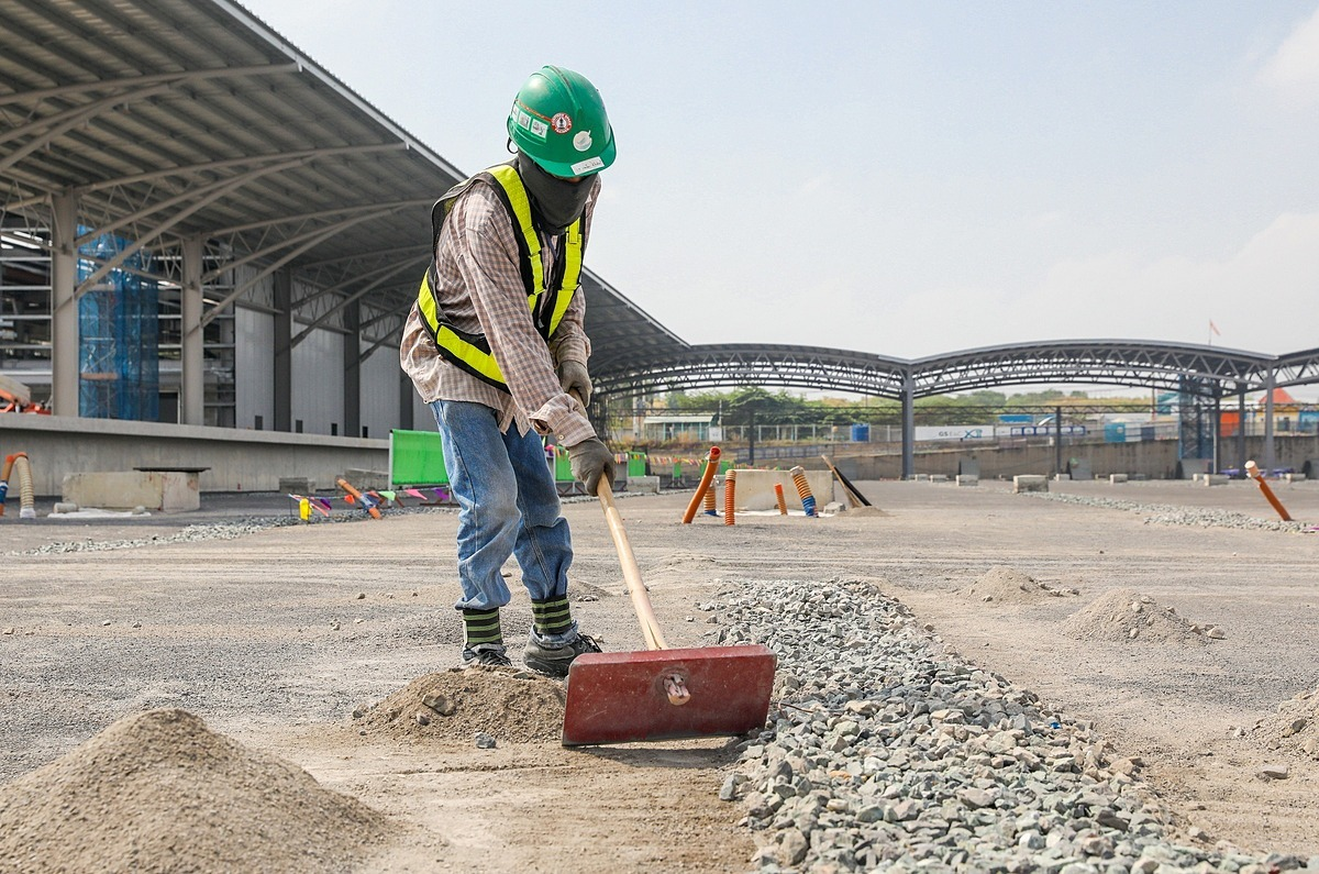 A worker spreads out stones to build water drainage trenches inside the trains parking space. Over 50 workers currently work inside the depot.Due to the ongoing Covid-19 pandemic, foreign experts of project involving the trains and equipment of the metro line have not bene allowed to enter Vietnam.