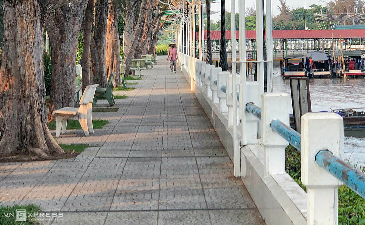 A woman in face mask walks on a deserted street in Ninh Kieu Port.