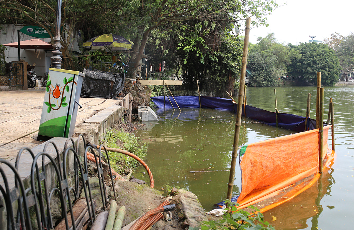 A section in Sword Lake is marked with tarpaulin fence for embankment upgrade near Thuy Ta restaurant. Photo by VnExpress/Tat Dinh