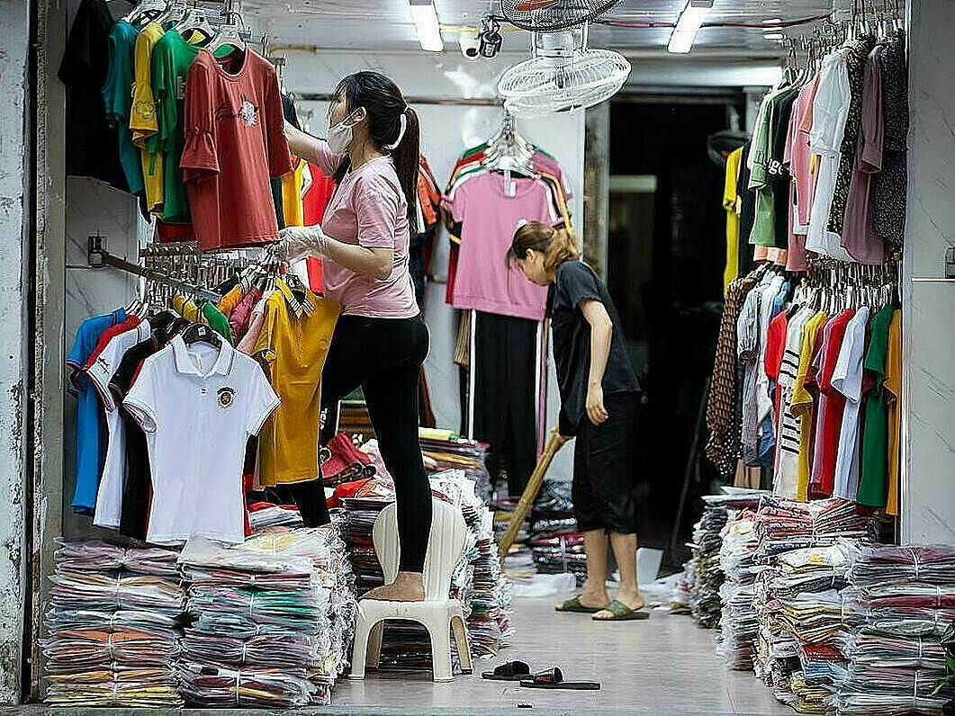 Staff members of a clothes store on Hang Dao Street are cleaning and preparing to welcome local buyers after closing their business for weeks. Thuong Tin and Me Linh Districts in the capital are still categorized as high-risk localities because they are still having active Covid-19 patients.