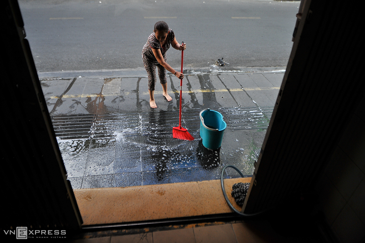 Owner of a pub on Saigonss Bui Vien Street cleans the sidewalk in front, preparing to open as the semi-lockdownn is lifted. Photo by VnExpress/Nguyet Nhi.