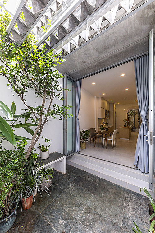 Not as harsh as its armour facade, the house offers a green space with trees and plants.