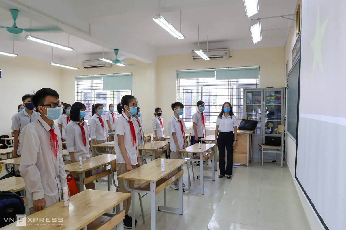 Students perform their flag salutations in their classrooms instead of on the school yard to prevent Covid-19 infection.