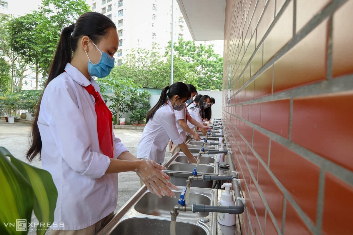 Students wash their hands at school.The schools timetable is adjusted so that there are only 3-4 periods a day, and break times are extended by 10 minutes so students would have more time to wash their hands and check body temperatures.