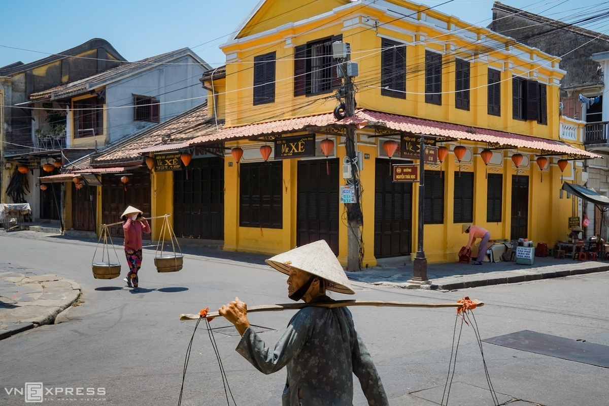 Two women with baskets on their shoulders walk on the crossroads of Nguyen Thai Hoc - Le Loi. The photo collection was taken by photographer Do Anh Vu to introduce peaceful and slow pace of life in Hoi An, a top tourist destination and hidden gem in Vietnam.