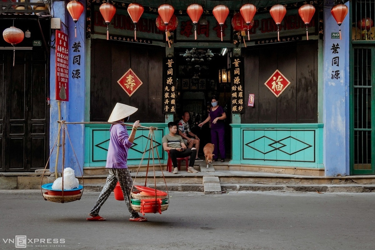 A woman carries a basket of rice cracker, a combination of baked coated cake, wet coated cake and some other materials, on her shoulder past a Chinese-style house on Nguyen Thai Hoc Street.