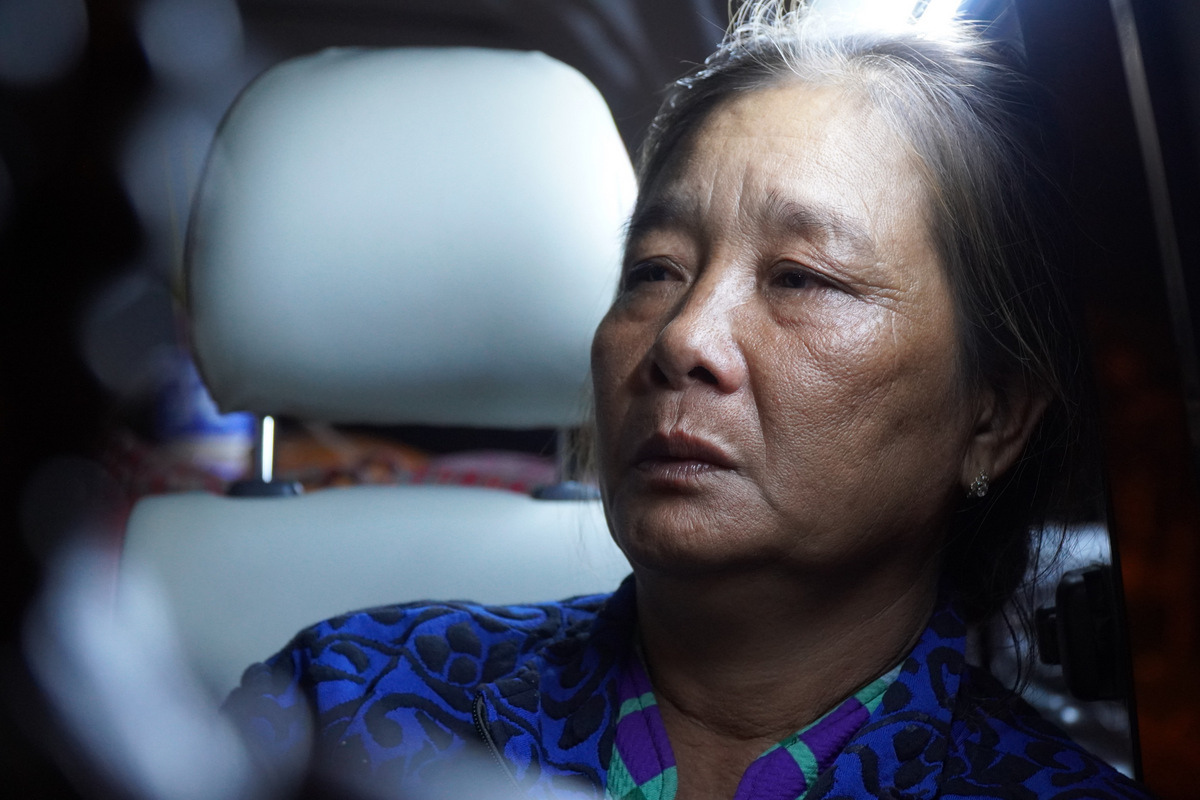 Suong sits on a car that carries the body of her husbands Nguyen Van Cuong back to their hometown in Ca Mau Province. Photo by VnExpress/Phuoc Tuan