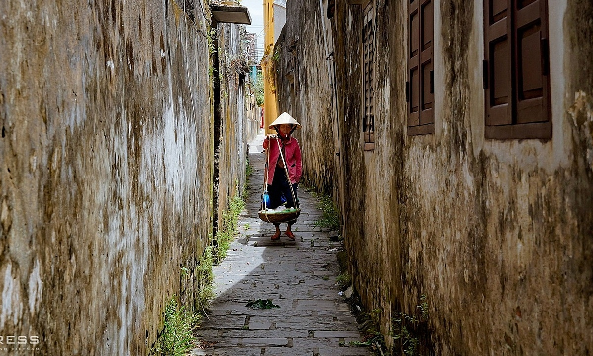 A woman with quang ganh on her should walks inside a mossy-covered small alley.