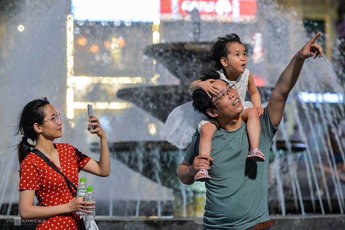 A family pose for a photo at the fountain right at Dong Kinh Nghia Thuc Square, a favorite shooting spot for visitors.