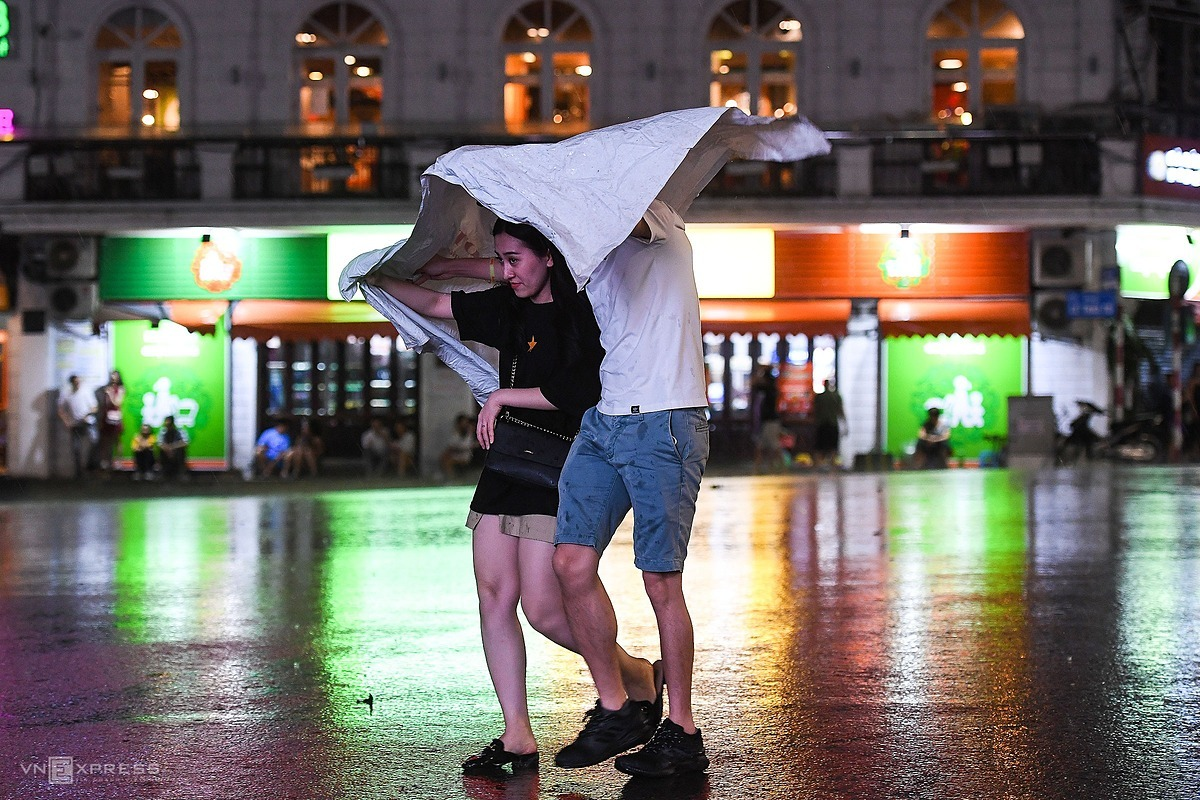 [Caption]aaA couple rush to find a shelter following a sudden downpour at 8:30 p.m. Friday.