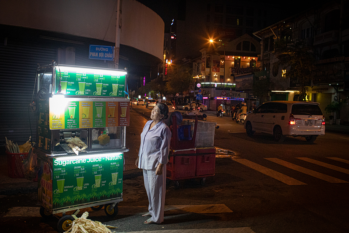 Duc, a smoothie and sugar cane juice seller, stands next to her cart with signs showing items and prices in English, Malaysian and Korean, May 16, 2020. Photo by VnExpress/Thanh Nguyen
