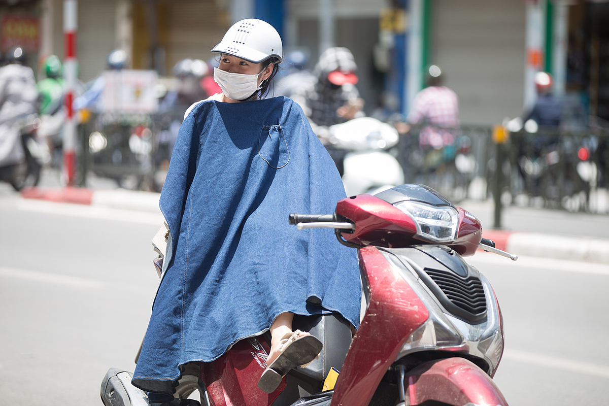 A girl in front of a store on Ton Duc Thang street protects herself from the sunlight using a piece of clothing as the UV index in Hanoi reached about 8-10.The UV Index is an international standard measurement of the strength of ultraviolet radiation from the sun. Between 0 and 3 is considered low and above 11 is deemed extreme with radiation that could burn skin and damage eyes within 20-30 minutes.