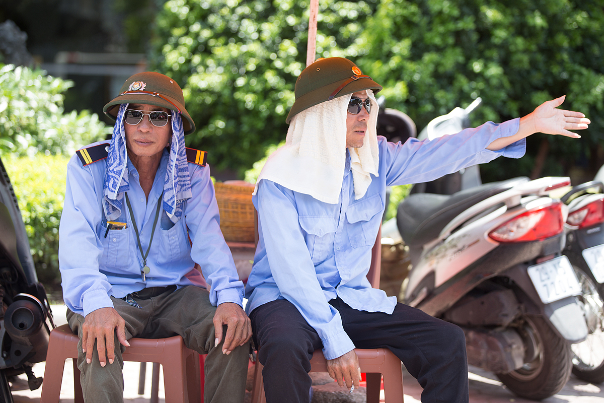 Nguyen Duc Chung (right) wears a hat and a cool towel to absorb sweat and avoid sunlight when working outdoors.
