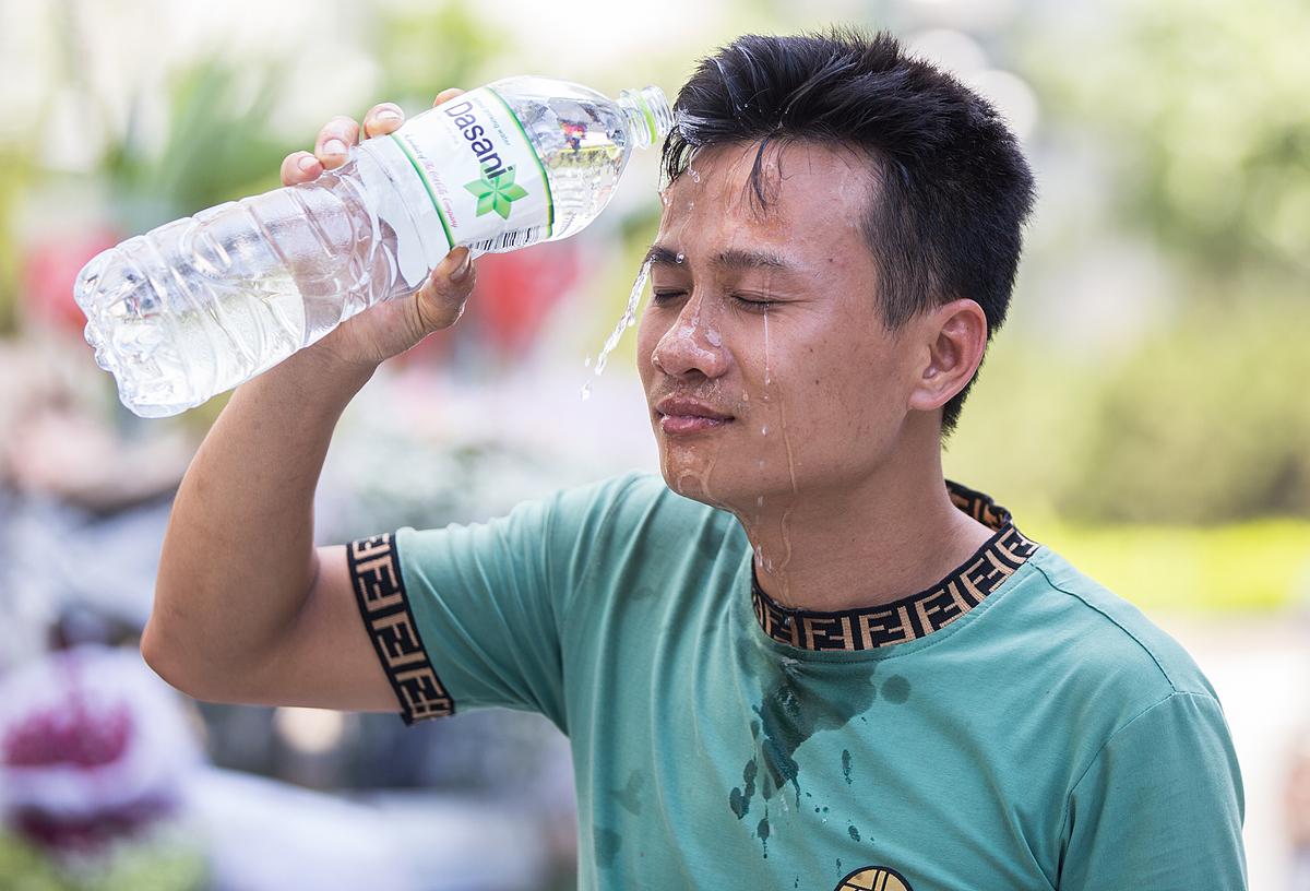 On Le Van Luong street, a man pours water on his face to cool down.