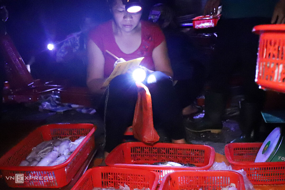 Headlamps shine on a 600-year-old seafood market in central Vietnam