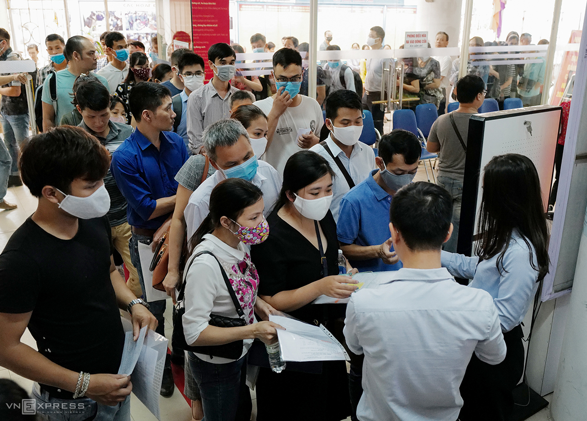 People rush into the center to get tickets that mark their ordinal numbers after the step of temperature check.