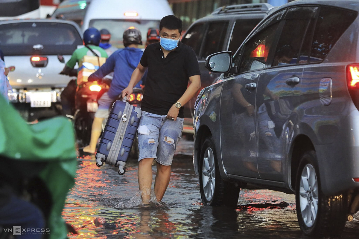 A man carries his suitcase along Dinh Bo Linh Street. He has to abandon his drive and wade through water to get into the Mien Dong (Eastern Region) Bus Station from where passengers travel to localities in Vietnam's southeast, the southcentral and the Central Highlands.