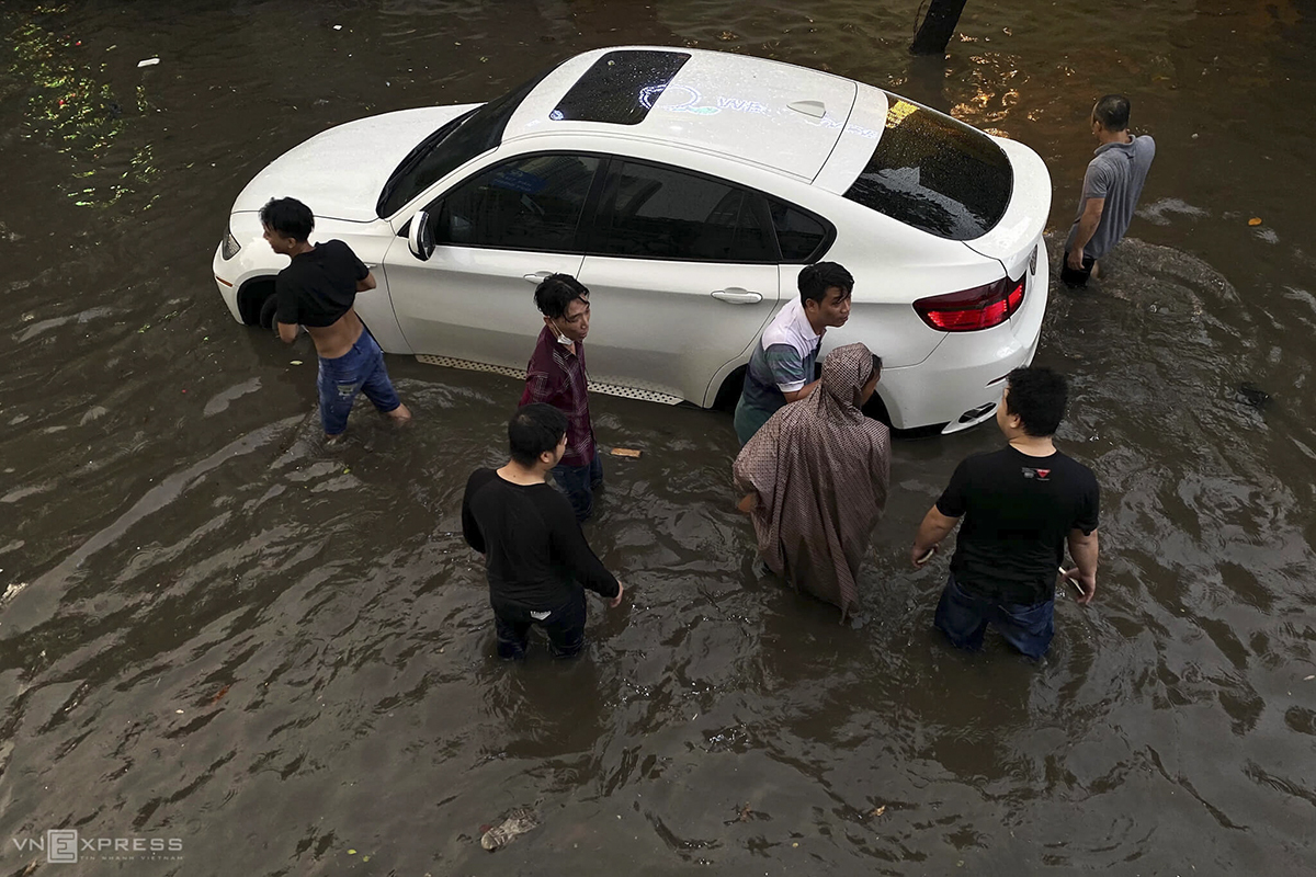 A car gets stuck in the middle of the flooded street after its engine was kill. The driver has got help from locals around to move it.