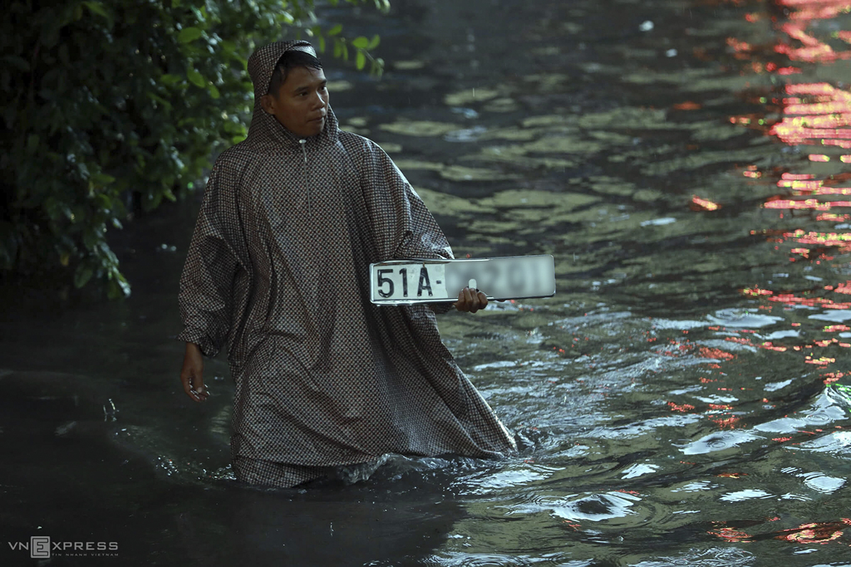 A man holds a number plate of a car he picked up from the flooded street.