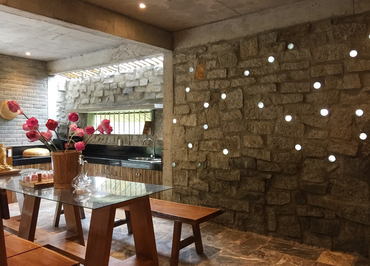 Holes in the stone wall allow light to enter the kitchen, in unison with aesthetics and eco-friendly living.