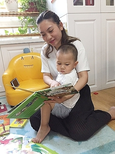 Doan Thi Quynh reads fairy tale for her son while at her home in Beijing. Photo courtesy of Quynh