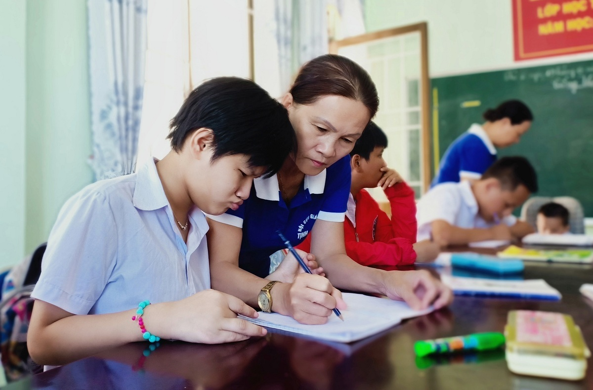 Pham Thi Kim Tuyen shows a student how to write a letter. Photo by VnExpress/Trong Quoc