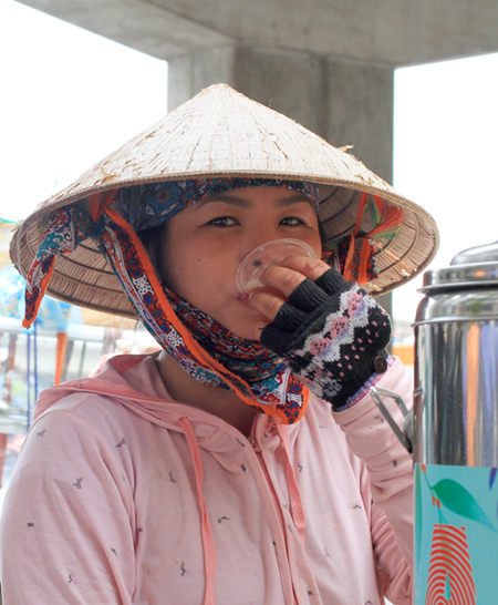 Lan drinks a cup of tea under scorching sun. Photo by VnExpress/Phan Duong.