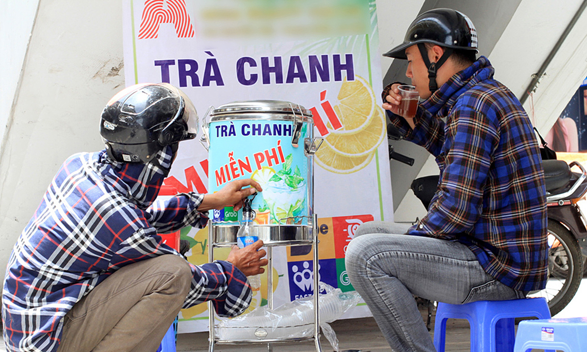 People take free iced tea from the stainless steel bottle. Photo by VnExpress/Phan Duong.