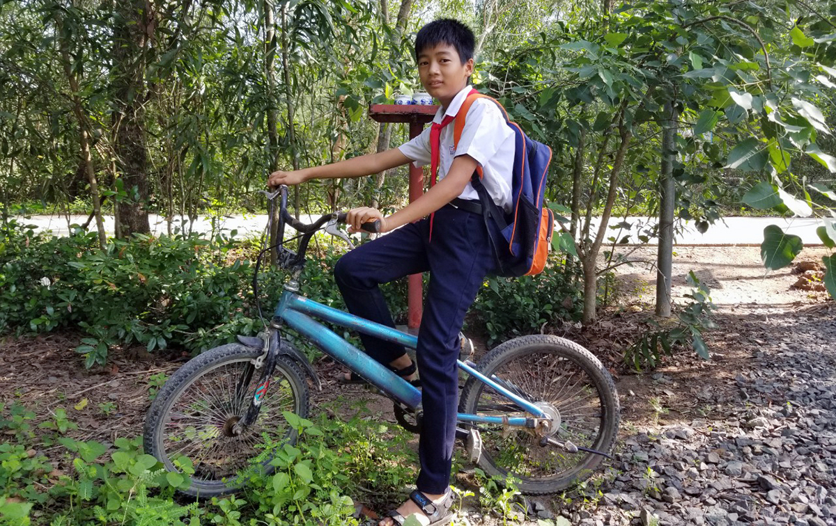 Pham Trong Dat on his bicycle wearing his school uniform and his backpack. Photo by Huynh Cong Lap.