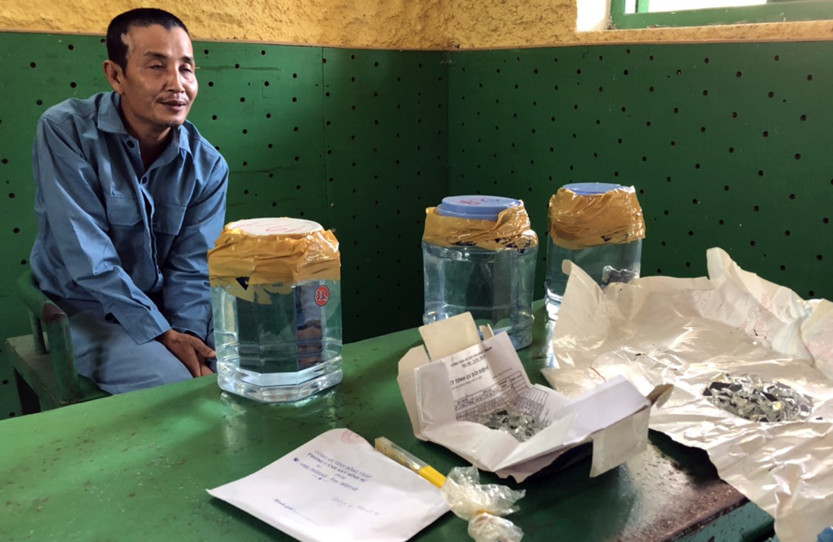 Truong Van Son and his fake meteorites in glass jars at the police station in Dong Thap Province. Photo by the police