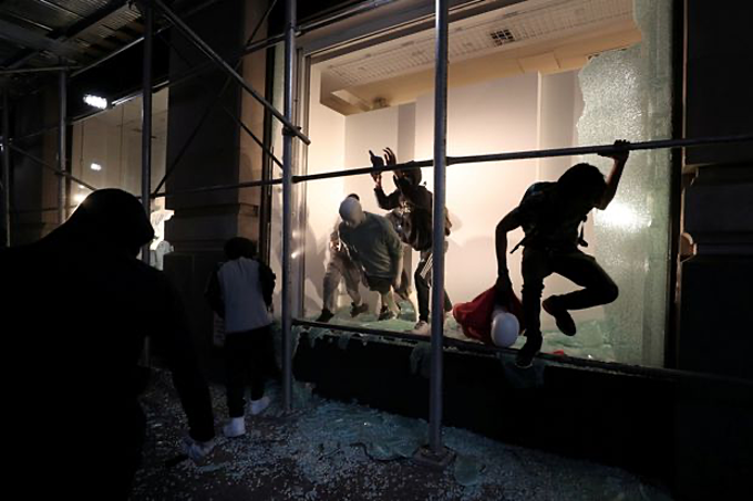 A man jumps from the window of a damaged store in New York on June 2, 2020 as protests against the death of George Floyd continue. Photo by Reuters/Jeenah Moon.