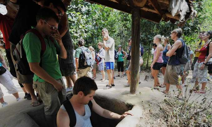 Foreign tourists climb into the underground network during a tour to Saigons Cu Chi Tunnels, 2018. Photo by AFP