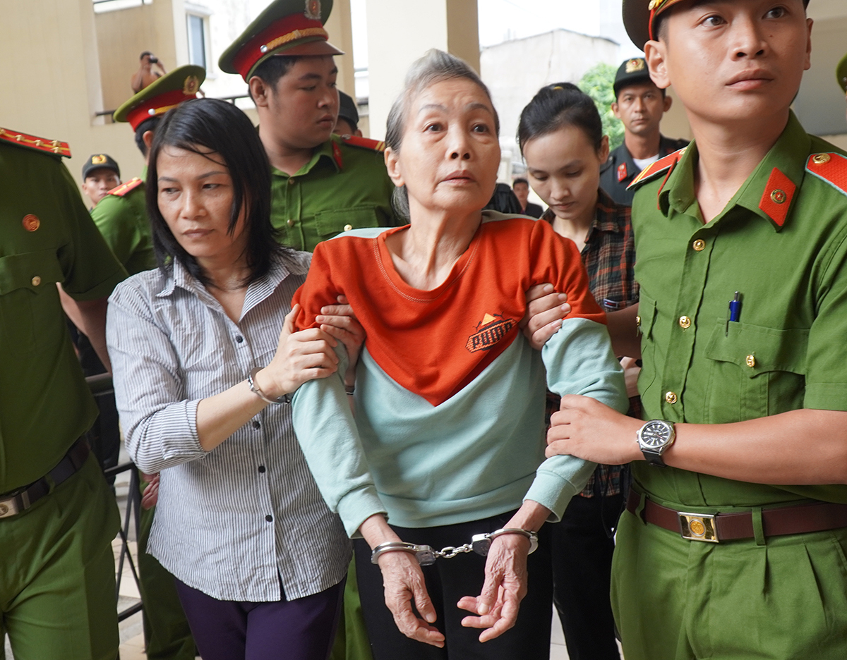 Nguyen Ngoc Tam Huyen (L) holds the arm of Trinh Thi Hong Hoa as Le Ngoc Phuong Thao is behind them when the three are escorted to the court in Binh Duong Province, July 3, 2020. Photo by VnExpress/Phuoc Tuan